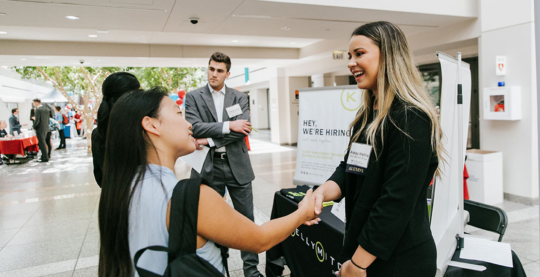 A student speaking to a representative at an event in University Hall