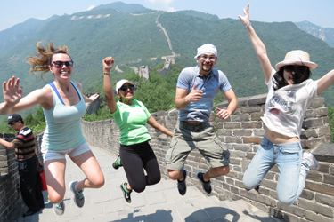 Students jumping in the air on top of the Great Wall of China